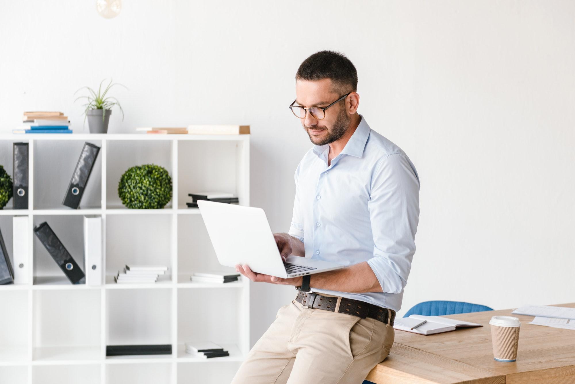 Image of businesslike man wearing white shirt sitting on table i